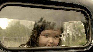 Photo : une très jeune fillette autochtone regarde par la fenêtre arrière d'un camion.