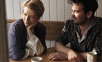 Photo officielle : une femme blonde (environ 35 ans on dirait) et un jeune homme (environ 25 ans) à une même table dans une maison, prenant un café. Il et elle porte des vêtements intérieurs chauds. Il a les cheveux noirs semi-courts et une légère barbe.