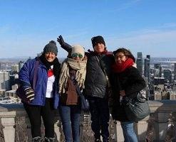 Photo: quatre adultes, côte à côte, vêtus pour l'hiver. Derrière, une grande ville plus bas, au soleil. Semblent être trois femmes et un homme. Elles/il viennent de pays d'Amérique du Sud.
