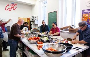 Photo de sept personnes dans la cuisine, autour d'une table avec des bols en métal et divers fruits et légumes. Logo CJC. Âges variés, etc.