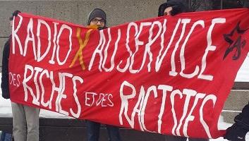 Trois jeunes hommes tiennent une grande bannière rouge : « Radio X au service des riches et des racistes ».