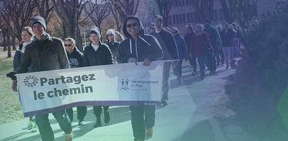 Photo : une centaine de jeunes adultes marchent avec une banderole « Partagez le chemin - Développement et Paix ». Un filtre triangulaire mauve et jaune-vert est ajouté.