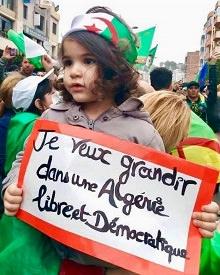 Photo d'une jeune enfant algérienne tenant une affiche : « Je veux grandir dans une Algérie libre et démocratique ». Elle a les cheveux bruns, un peu frisés aux bouts, et a un bandeau aux couleurs du pays. Une foule derrière elle (manif).