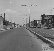 Photo en noir/blanc du boulevard Charest dans la partie du quartier Saint-Sauveur : quelques habituations carrées, mais on voit surtout le béton et les lampadaires doubles.