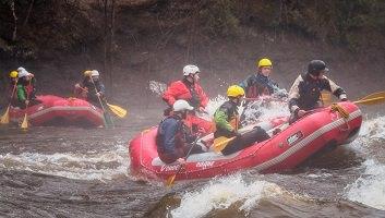 Photo : deux « rafts » rouge (petites embarcations gonflables), sur une rivière d'eau agitée. Six personnes par embarcation portant des casques protecteurs.