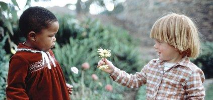 Photo : un jeune garçon blanc et blond (cheveux mi-longs) donne une fleur à une fillette noire aux cheveux courts en robe rouge-brune. Elle/Il sont dans un jardin vert.