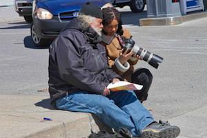 Photo : deux personnes assieds sur un trottoir près de voitures. Une jeune femme, peau brune, tenant une caméra et la montrant à un monsieur aux cheveux et barbes blanches et tenant des feuilles de papier.