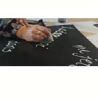 Petite photo : une main écrit un mot, en blanc, sur un tableau noir.