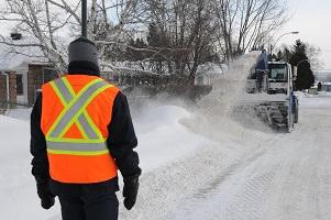 Photo d'une machine de déneigement de rue à peine visible au travers la neige ; un travailleur portant une veste orange et jaune surveille ; maison ; arbres.