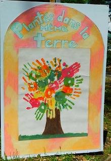 Peinture sur une pancarte blanche : « Plantés dans la même terre ». Plusieurs empreintes de mains, de couleurs différentes, forment les branches et feuillage d'un arbre. Autour, des motifs orange et rouges nuageux.