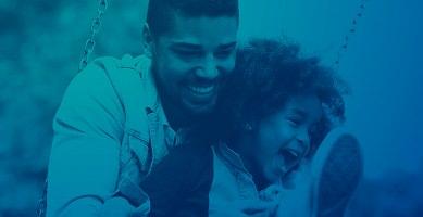 Photo vue à travers filtre bleu saturé : un jeune père sur une balançoire avec jeune fille très souriante. Aire naturelle et joviale. Il/elle ont la peau foncée.