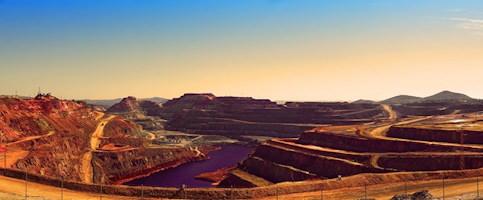 Photo panoramique : vaste mine à ciel ouvert, de sable orangé, en étages. Une rivière ou lac mauve au bas.