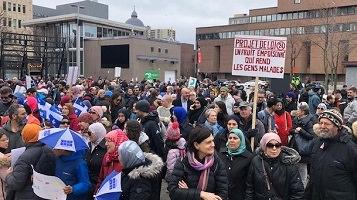 Manif à Montréal contre le projet de loi 21. Foule dense, varié en genres et styles, dont des femmes portant le foulard de style musulman. Drapeaux du Québec ici et là.