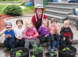 Photo : six enfants, souriants, comiques, asseyent ensemble. Madame Jardine derrière: chapeau de paille, lunettes, souriante. C'est dehors l'été. Pots noirs avec plants verts.