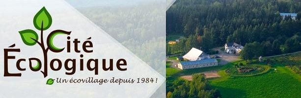 Bannière sur fond de photo aérienne du terrain vert, fermes, maisons et forêt verte. « Cité écologique - un écovillage depuis 1984 »