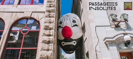 Affichette sur fond d'une photo : un ballon géant, représentant une tête de clown, est coincé entre deux murs d'immeubles (ruelle). « Passages Insolites ».</body></html>