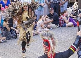 Photo : une femme souriante et un homme de dos, vêtus de cuir beige et de plumes, dansent ensemble. Autour, une foule d'enfants et parents.
