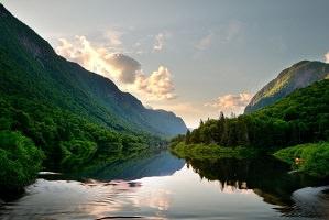 Photo officielle : rivière calme dans une vallée très verte, forêt de conifères, montagnes non loin et quelques nuages. Soleil derrière les montagnes.