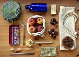 Photo : table en bois, vue de haut, sur laquelle sont posé soigneusement plusieurs objets, dont pommes, noix, brosse, etc.