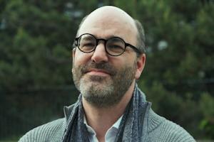Photo de M. Deneault devant des arbres verts. Lunettes noires rondes, barbe légère, air souriant, presque chauve.