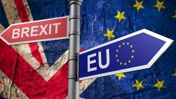 Affichette sur fond de parties des drapeaux des R-U et de l'UE. Une fléchette de signalisation indique Brexit en rouge d'un côté et EU en bleu de l'autre.