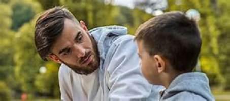 Photo : un jeune homme, légèrement barbu, écoute attentivement un jeune garçon. Les deux portent des gilets de coton ouaté.</body></html>