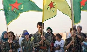 Des femmes et hommes militaires kurdes, tenant des drapeaux du YPJ et YGP, baissent la tête pour honorer les défunts. Une foule civile derrière.