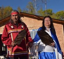 Photo : monsieur Petiquay et madame Biroté, portant des vêtements un peu cérémoniel autochtone (chemise rouge ornementé pour lui, cape bleu pour elle). Les deux tiennent des grandes plumes brunes.