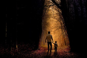 Photo d'un homme tenant la main d'un enfant, les deux marchent dans une forêt très sombre, noire, mais une lumière du ciel éclaire un chemin au centre.