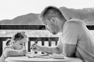 Photo en noir et blanc d'un père dessinant avec sa petite. Il a les cheveux courts et t-shirt blanc.</body></html>