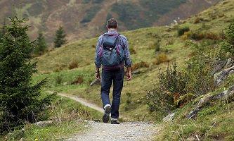 Photo : sur un chemin en forêt montagneuse, un homme de dos, avec sac-à-dos, marche sur un étroit chemin.