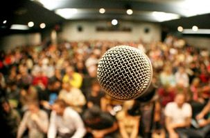 Photo d'un micro devant une salle comble. Le focus est sur le micro et la foule assise derrière est floue.