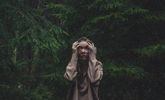 Photo : dans une forêt dense de sapins verts foncés, une jeune femme dans la pluie pose ses mains sur sa tête et semble perdue.