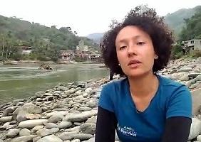 Photo d'Isabel Zuleta accroupie sur les berges rocheuses d'une rivière et parlant à la caméra. T-shirt bleu, cheveux bruns frisés semi-courts, environ 30 ans et jolie.