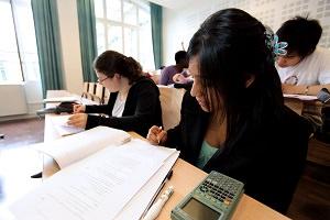 Des femmes adultes, dans la trentaine, écrivent de manière studieuse sur leur cahier, sur des pupitres de classe.