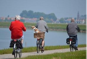 Photo de trois personnes âgées en vélo, dont un chien dans un panier arrière, sur le bord d'une large rivière avec des maisons au loin au toits orange.