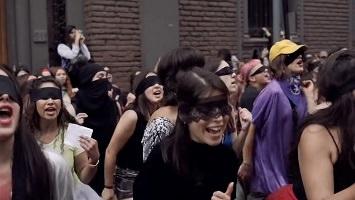 Photo : foule de femmes chiliennes, les yeux bandés, en environ cinq rangées, dansant, chantant, souriantes.