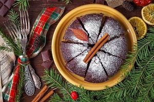 Photo : sur une table en bois brun, au bord de tiges d'arbres conifères, un plat en céramique avec un gâteau brun.