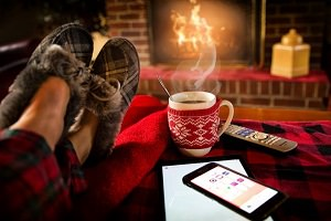 Photo de pieds en pantoufle sur une couverture rouge rayée noir, tasse rouge de café, cellulaire.