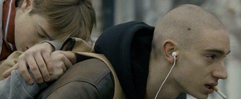 Photo officielle tirée du film : un jeune homme semble épuisé, les yeux fermés, couché sur le dos d'un autre jeune homme chauve, écouteurs dans les oreilles, et cigarette à la bouche.