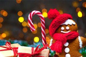 Photo : petit bonhomme de pain d'épice portant un bonnet rouge et tenant une canne à sucre, au côté de boîtes à cadeaux.