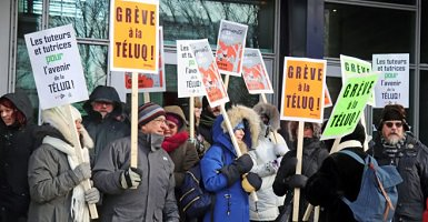 Photo de la manif du syndicat près de l'entrée du bâtiment. On y voit plus de dix personnes vêtues pour le grand froid. Pancartes diverses dont notamment « Les tuteurs et tutrices pour l'avenir de la TÉLUQ ! »