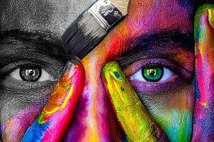 Photo d'un visage vu de près : nez et yeux, un côté gris, un côté multicolore vif, dont l'oeil vert forêt.</body></html>