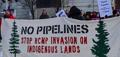 Photo d'une manif sur une voie ferrée, l'hiver, avec bannière beige « No pipelines - Stop RCMP invasion on indigenous lands ». Dessin de deux sapins verts sur la bannière. Foule derrière.