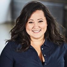 Portrait Manal Drissi : cheveux longs bruns, souriante, chemise bleu marin.