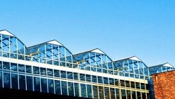 Photo d'une grande serre vitrée sur un toit d'immeuble en briques rouges.