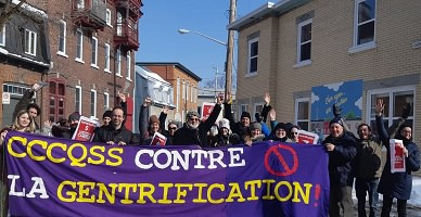 Photo d'une trentaine de personnes devant les bureaux du CCCQSS, au soleil, avec une bannière violet « CCCQSS contre la gentrification ». Des gens tiennent aussi les petites affiches rouges en question.