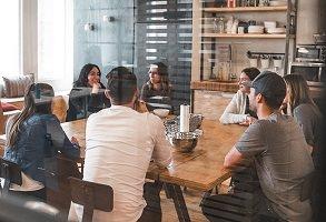 Photo de sept jeunes adultes autour d'une grande table en bois dans un café ensoleillé.