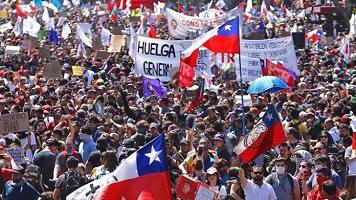 Photo d'une grande foule très dense arborant des drapeaux du Chili, etc.
