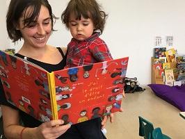 Photo d'une jeune femme tenant un-e gamin-e d'environ 2-3 ans, aux cheveux longs bruns ébouriffés un peu et chemise rouge; et tenant aussi un grand livre rouge avec plusieurs personnages dessinés dessus.